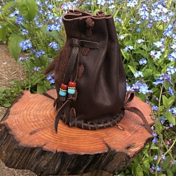 Brown leather barrel bag with feathers back view