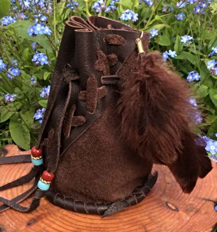 Brown leather barrel bag with feathers close up